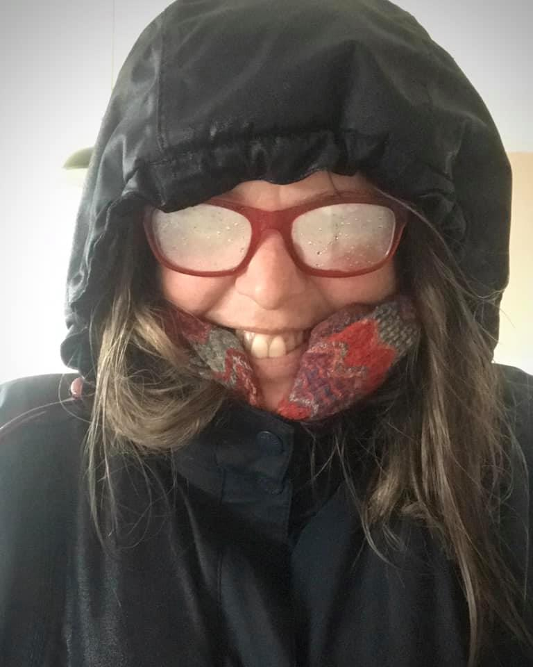 Caitlin, a white woman, has been caught in a storm - her red glasses are all steamed up and her blue waterproof coat and hood look black because it's so wet!