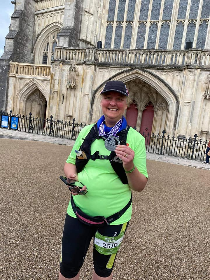 Carmen is hot and rosy-cheeked, standing in capri pants and a bright lime green t-shirt, proudly holding her finisher's medal in front of Winchester Cathedral. Her smile is broad